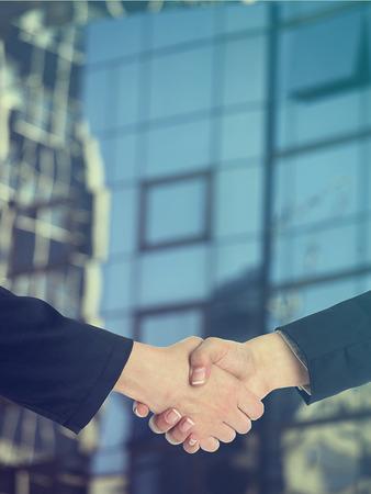 building trust: Handshake Handshaking and blured building in background Stock Photo