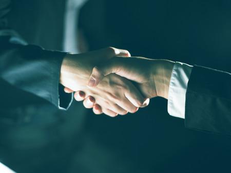 good bey: Handshake Handshaking light and dark Stock Photo