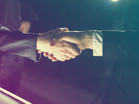 black handshake: Handshake Handshaking light and dark Stock Photo