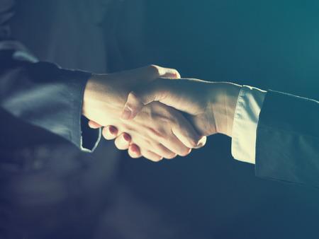 negociacion: Apretón de manos del apretón de manos oscuras y claras