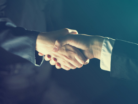 negotiation business: Handshake Handshaking dark and light Stock Photo