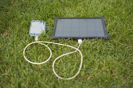 energy use: Use of renewable energy - Mobile Phone Chargers on grass in nature with Sun Stock Photo