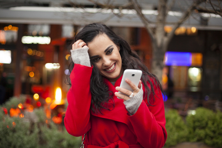 lady in red: Traveling Smiling Woman in Red Coat hold Mobile Phone, smartphone In City, Urban Space, noise on image Stock Photo