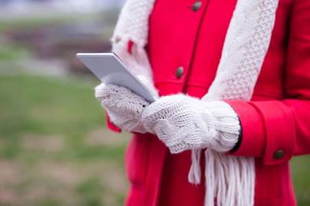 Woman in wool gloves hold tablet smart-phone. Cold Weather