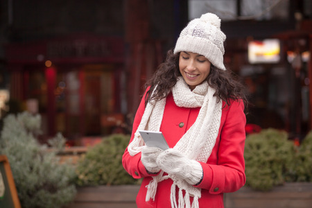 Beautiful Woman in Red Coat and and wool cap and gloves read messages on smartphone and smiling. Urban Space. Cold Weather