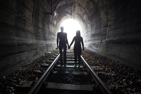 hidden danger: Couple walking hand in hand along the track through a railway tunnel towards the bright light at the other end, they appear as silhouettes against the light