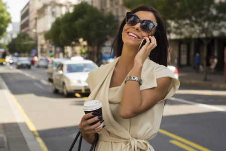 Fashionable young brunette wearing white dress and sunglasses laughs into phone on street, city, urban space photo