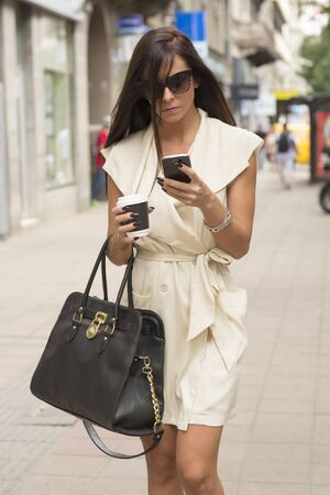 Stylish young business woman wearing short white dress and sunglasses texts in urban setting while holding coffee and bag photo