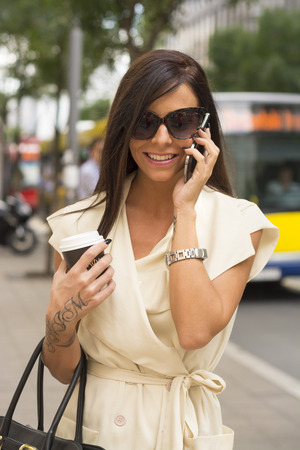 Fashionable young brunette wearing short white dress and sunglasses laughs into phone on city street near bus photo