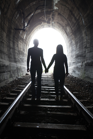 emigranti: Couple walking hand in hand along the track through a railway tunnel towards the bright light at the other end, they appear as silhouettes against the light