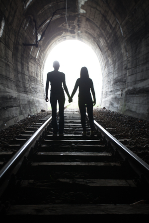 emigranti: Coppie che camminano mano nella mano lungo la pista attraverso un tunnel ferroviario verso la luce brillante all'altra estremità, appaiono come sagome contro la luce