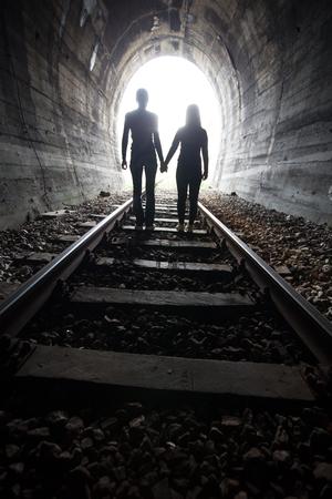emigranti: Coppie che camminano mano nella mano lungo la pista attraverso un tunnel ferroviario verso la luce brillante all'altra estremit�, appaiono come sagome contro la luce
