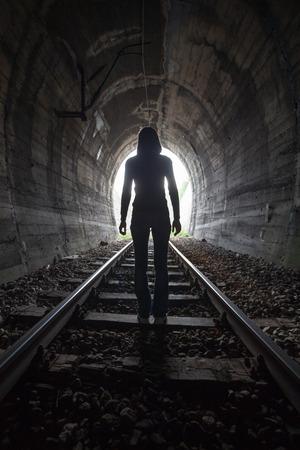 Hombre que se perfilan en un túnel de pie en el centro de las vías del tren que mira hacia la luz al final del túnel en una imagen conceptual