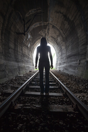 bright light: Man silhouetted in a tunnel standing in the center of the railway tracks looking towards the light at the end of the tunnel in a conceptual image