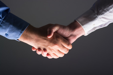 camaraderie: Low angle view of two businessmen hands shaking over dark gray background and light source at bottom side
