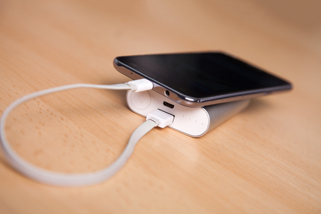 Mobile Phone Charging With Power Bank on wooden table Stock Photo