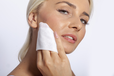 Young woman clean face and eyes with wet wipes, remove make-up, body breast lingerie Imagens