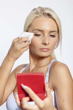 Young woman clean face and eyes with wet wipes, holding mirror, remove make-up, body breast lingerie Standard-Bild - 119387075