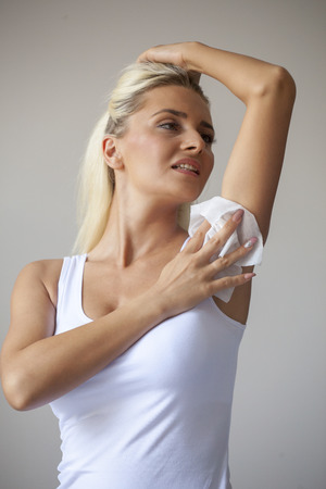 Blonde woman in white shirt wiping the armpit with wet wipes, perspiration, sweat Standard-Bild - 119387118