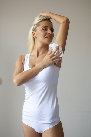 Blonde woman in white shirt wiping the armpit with wet wipes, perspiration, sweat Standard-Bild - 119387337