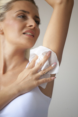 Woman in white shirt wiping the armpit with wet wipes, perspiration, sweat Imagens