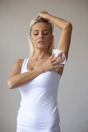Woman in white shirt wiping the armpit with wet wipes, perspiration, sweat Banco de Imagens