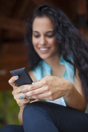 Social networking - mixed race young smiling woman use smart-phone. He uses the phone to be in touch with his friends. Focus on phone Standard-Bild - 119387498