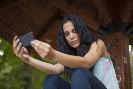 Social networking - mixed race young smiling woman use smart-phone. He uses the phone to be in touch with his friends Standard-Bild - 119387504