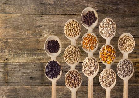 Different type of seeds on wooden spoon. Wooden background Standard-Bild - 104914104
