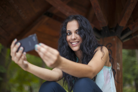 Social networking - mixed race young smiling woman use smart-phone. He uses the phone to be in touch with his friends Standard-Bild - 119387510