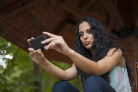Social networking - mixed race young woman use smart-phone. He uses the phone to be in touch with his friends Standard-Bild - 119387630
