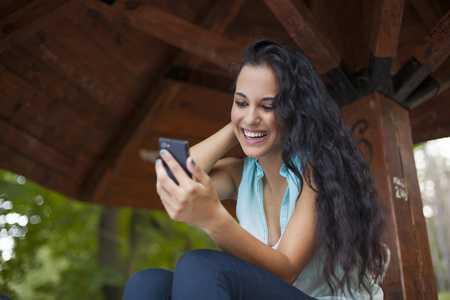 Social networking - mixed race young smiling woman use smart-phone. He uses the phone to be in touch with his friends Standard-Bild - 119387632
