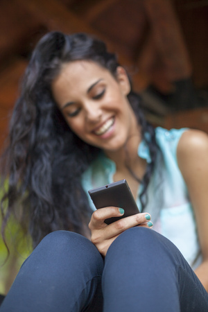 Social networking - mixed race young smiling woman use smart-phone. He uses the phone to be in touch with his friends Standard-Bild - 119387640
