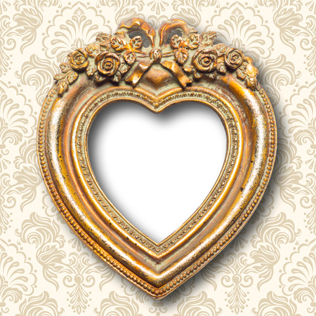 Old memories - old gold heart shape picture frame on pattern wall Standard-Bild - 119387966