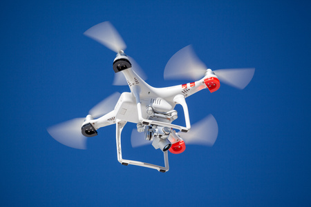 Quadrocopter drone with camera on blue clear sky recording photo and video Standard-Bild - 119387979