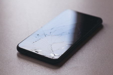 Phone with broken touch-screen screen on black table desktop