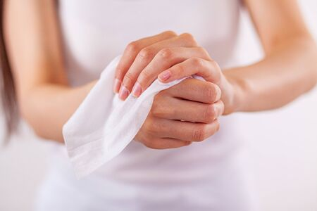 Close-up scene: woman cleaning hands with wet wipes, white Stock Photo