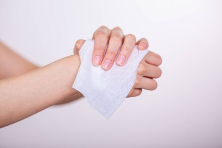Fingers hold wet wipes and cleaning hands, white background, studio shot.