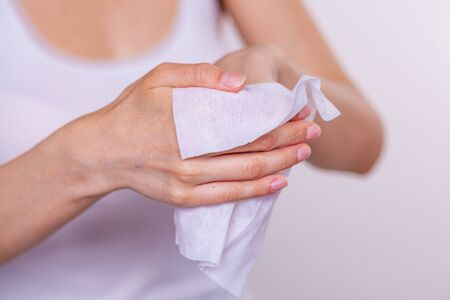 Close-up of cleaning hands with wet wipes, white Stock Photo