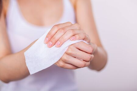 Young women cleaning hands with wet wipes, white Stock Photo - 126259499