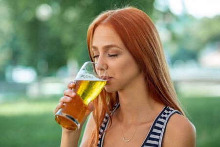 Beautiful Cute Red-hair Women Drinking Beer in nature, public, outdoor, summer Stock Photo