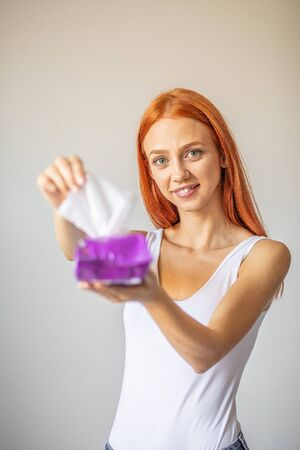 Wet wipes are universal an practical: red-hair women take one wipe from big package for cleaning