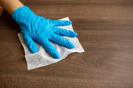 Woman's hand in blue gloves sanitizing cleaning home office wood table surface with wet wipes