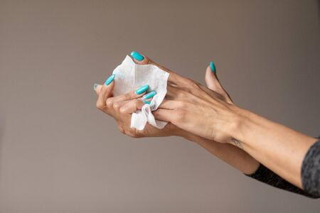 Old woman gently cleaning hands with wet wipes, white