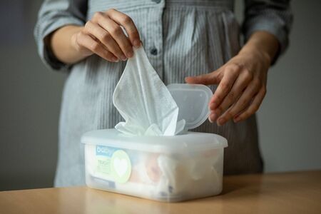 Wet wipes are universal an practical: woman hand take one wipe from big plastic box package for cleaning, home, indoor Stock fotó