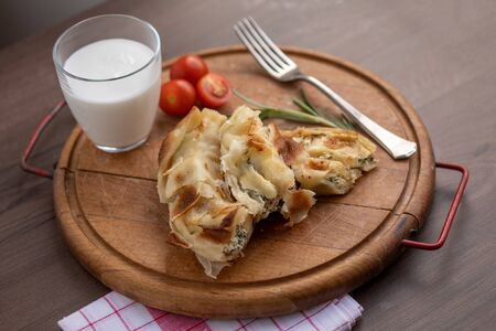 Traditional balkan breakfast - Burek pie with cheese and spinach served on vooden table Stock fotó