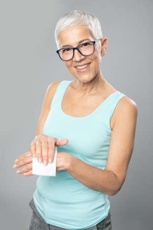 Senior woman cleaning hands with wet wipes - care for health and prevention of infectious diseases stock photo