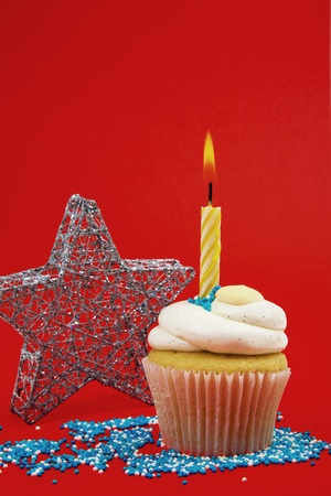 Cupcake With Candle And Star On Red Background Stock Photo - 8364344