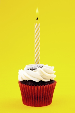 Cupcake With Candle On Yellow Background photo