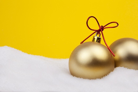 Christmas Golden Balls With Red Cord And Snow On Yellow Background photo